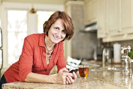 Smiling mature woman using mobile phone in kitchen at home Stock Photo - 19523248