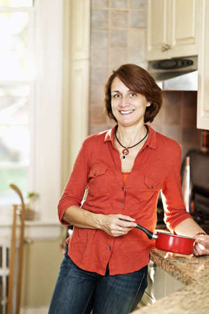 Smiling mature woman enjoying cooking in kitchen at home Stock Photo - 19535941