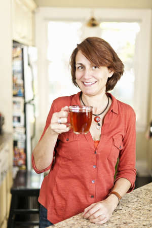 Smiling mature woman holding cup of tea in kitchen at home Stock Photo - 19523078
