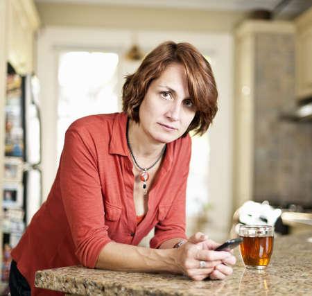 自宅の台所で携帯電話を保持している心配の成熟した女性 写真素材