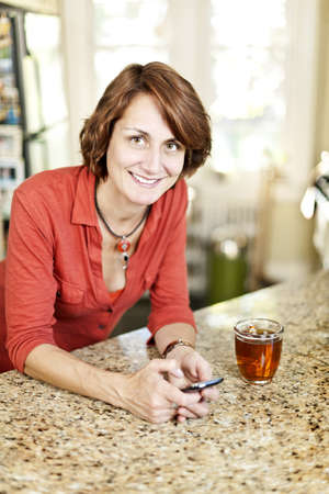 Smiling mature woman using mobile phone in kitchen at home Stock Photo - 19523105