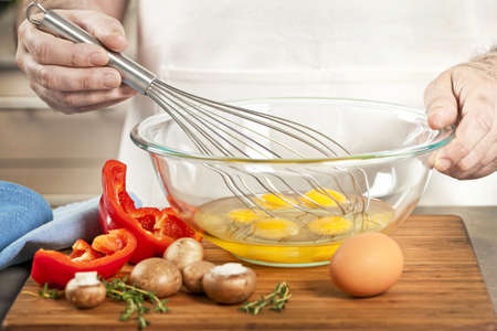 beating: Closeup on mans hands whisking eggs in bowl for cooking omelet with vegetables