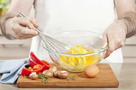scramble: Closeup on mans hands whisking eggs in bowl for cooking omelet with vegetables