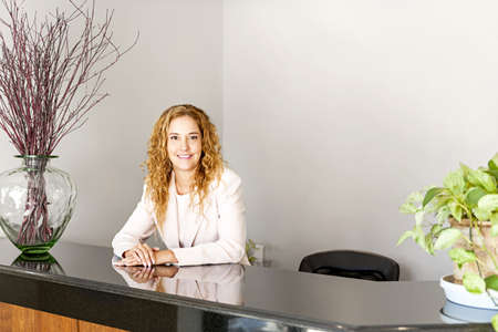 Receptionist standing at reception counter in office photo