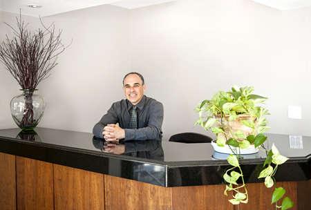 Businessman standing at reception counter in office Standard-Bild
