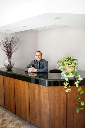 Businessman standing at reception counter in office photo