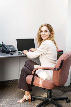 Happy businesswoman sitting at workstation in office with computer Stock Photo - 19535947
