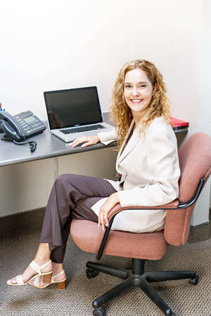 cubby: Happy businesswoman sitting at workstation in office with computer