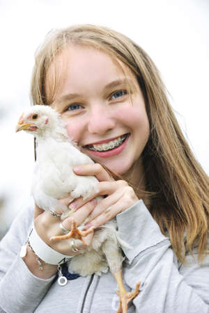 Smiling teenage girl with braces holding young chicken photo