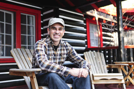 adirondack chair: Smiling man sitting on cottage deck in wooden adirondack chair