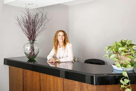 recepcionista: Recepcionista de pie en el mostrador de recepci?n en la oficina