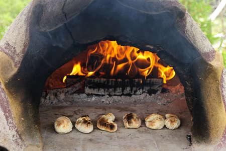 haciendo pan: Piedra horno de leña en el fuego para hornear pan casero recién hecho