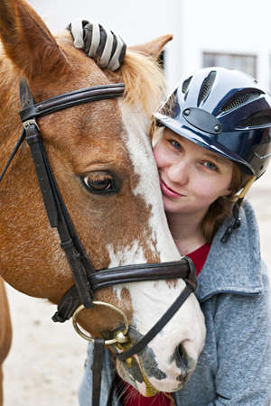 Portrait of young woman rider with brown horse