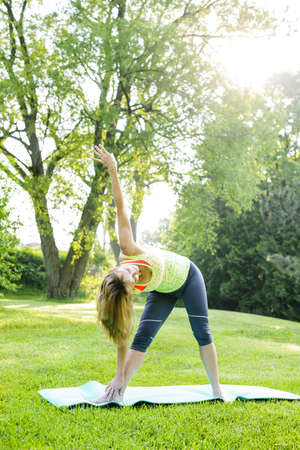 Female fitness instructor doing yoga extended triangle pose outdoors in green park photo