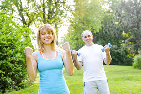 exercising: Female fitness instructor exercising with middle aged man in green park Stock Photo