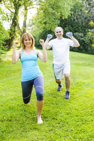 Female fitness instructor exercising with middle aged man in green park photo