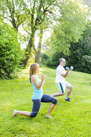 Female fitness instructor exercising with middle aged man outdoors in green park Zdjęcie Seryjne - 20112399