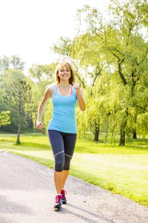 caminando: Sonriente mujer en el ejercicio de correr camino en el parque verde de verano