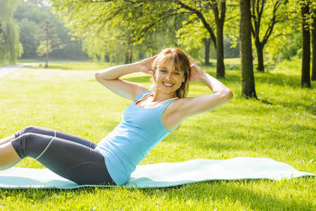 Female fitness instructor exercising doing sit-ups on yoga mat outside in green summer park photo