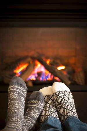 Feet in wool socks warming by cozy fire Standard-Bild