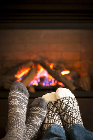 christmas fireplace: Feet in wool socks warming by cozy fire Stock Photo