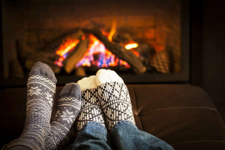 heat home: Feet in wool socks warming by cozy fire Stock Photo