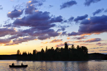 algonquin park: Silhouette of island and canoe on lake at sunset in Algonquin Park, Canada