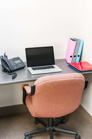cubby: Workstation in office with swivel chair desk and laptop computer