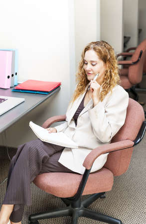 Businesswoman thinking of ideas in office workstation photo
