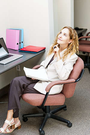 Businesswoman thinking of ideas in office workstation looking up photo