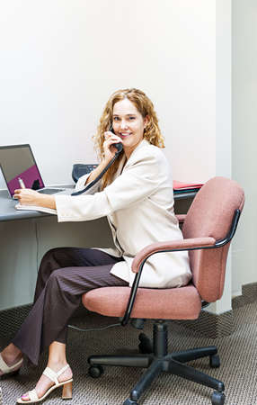 Businesswoman on phone talking and taking notes in office workstation photo