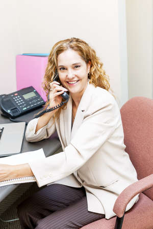 Smiling businesswoman on phone in office workstation photo