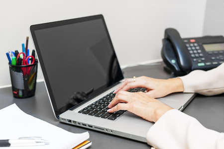 cubicle: Female hands typing on laptop keyboard at office desk Stock Photo