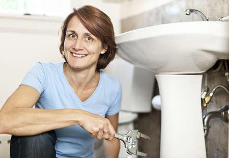 Zekere vrouw repareren wastafel in de badkamer thuis