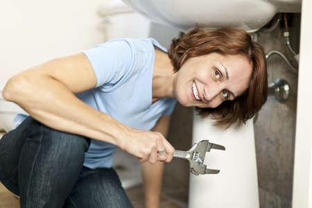 Zekere vrouw repareren wastafel in de badkamer thuis Stockfoto