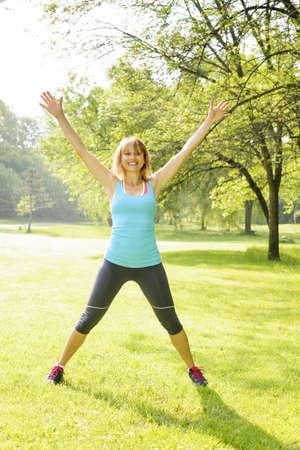 Female fitness instructor doing jumping jacks exercising in green park
