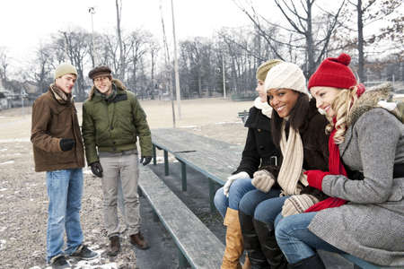 Two young men looking at three pretty women in winter park Stock Photo