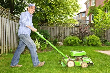 Man met gazon maaier in aangelegde achtertuin