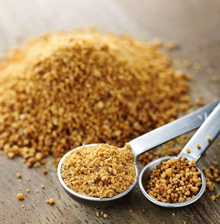 Organic coconut palm sugar in measuring spoons Standard-Bild