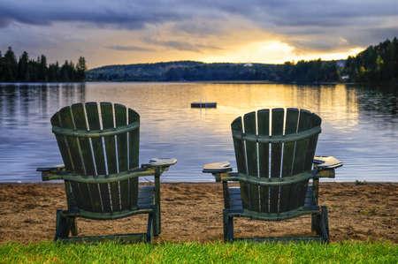 穏かな湖で夕焼けのビーチで 2 つの木製の椅子。アルゴンキン州立公園、カナダ。