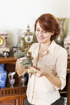 Happy caucasian woman proudly polishing antique collection