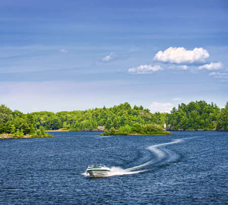 Woman piloting motorboat on lake in Georgian Bay, Ontario, Canada