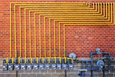 Fila de los medidores de gas natural con tubos de color amarillo en la pared de ladrillo de construcción