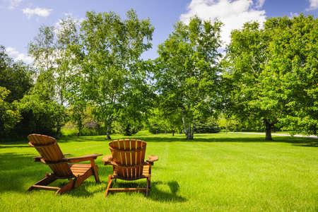 Twee houten Adirondack stoelen op weelderig groen gazon met bomen Stockfoto