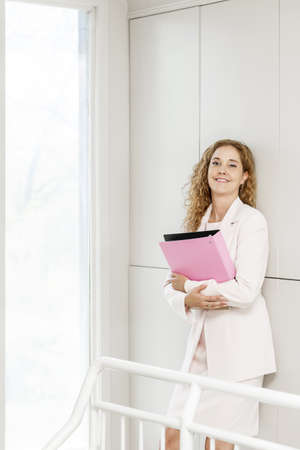 Happy confident business woman standing in office hallway holding binder Banque d'images