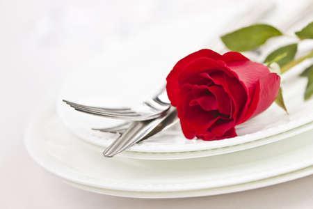プレート上の赤いバラとロマンチックなレストランのテーブルの設定