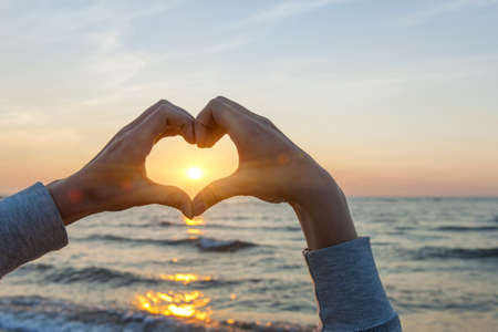 Handen en vingers in hartvorm framing ondergaande zon bij zonsondergang over de oceaan Stockfoto