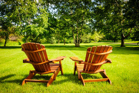 Two wooden adirondack chairs on lush green lawn with trees