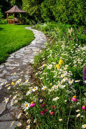 Wildflower garden with paved path leading to gazebo and blooming daisies