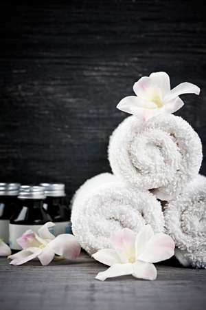 White rolled up towels with body care products at spa Фото со стока